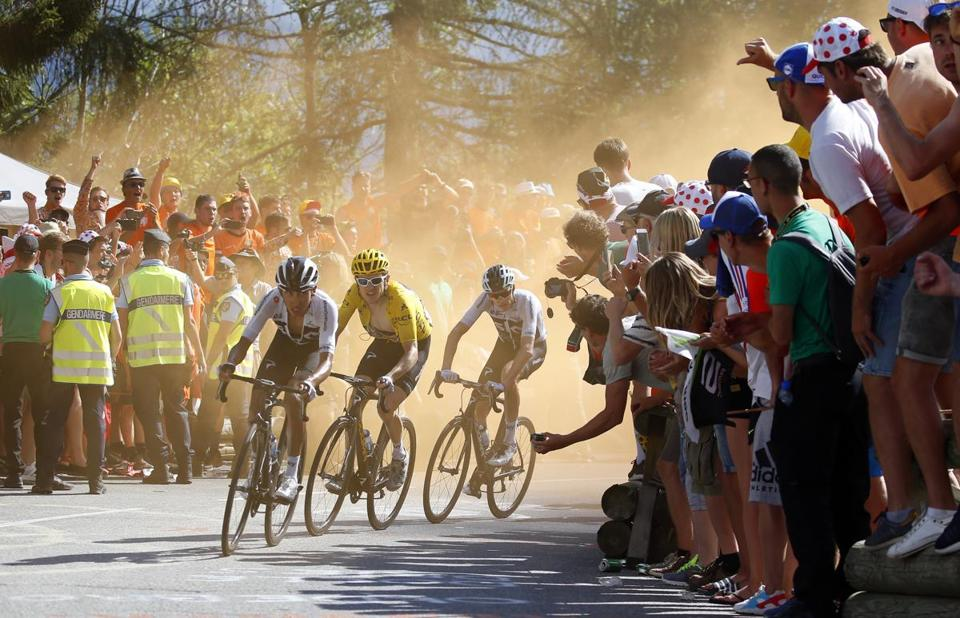 Fans lean in as leader Geraint Thomas and two other racers turn a corner