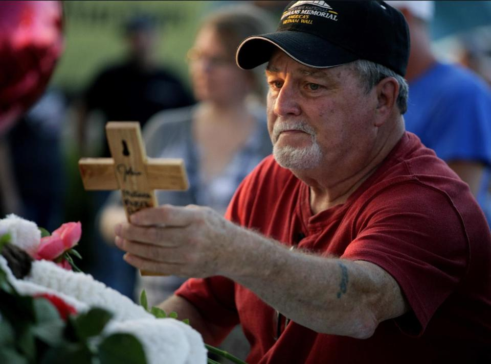 Russ Mc Kay looked at a cross left in a makeshift memorial for his friends before a candlelight vigil in the parking lot of Ride the Ducks Friday in Branson Mo on Friday