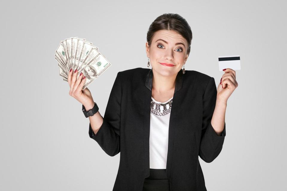 Businesswoman showing at cash, dollar and credit card. Studio shot, indoor. Isolated on grey background