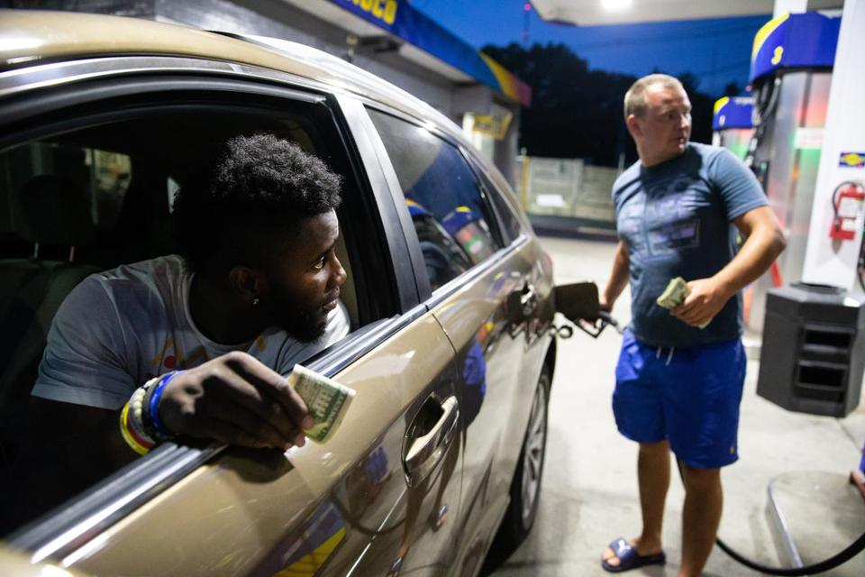 08/07/2018 NEWTON, MA Ceasar Adim (cq) (left) of Boston, waits to pay attendant Oleg Zhovnirchyk (cq) at the Sunoco station owned by Ed Negoshian in Newton. The station offers a discount for customers paying in cash. (Aram Boghosian for The Boston Globe)