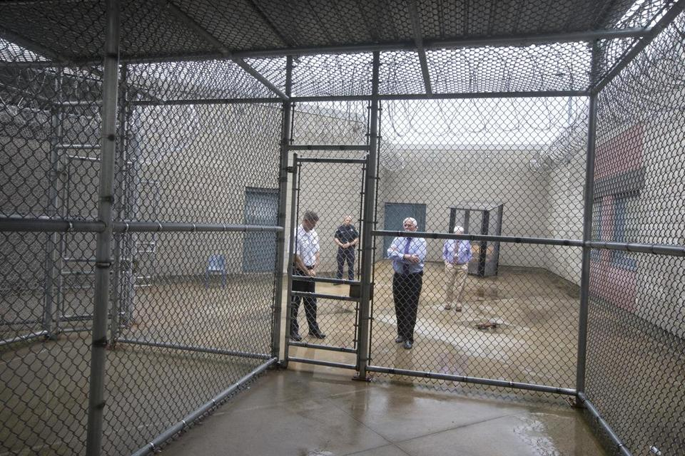 Sheriff Thomas Hodgson, third from left, stands in front of the exercise cage at the Bristol County House of Corrections.