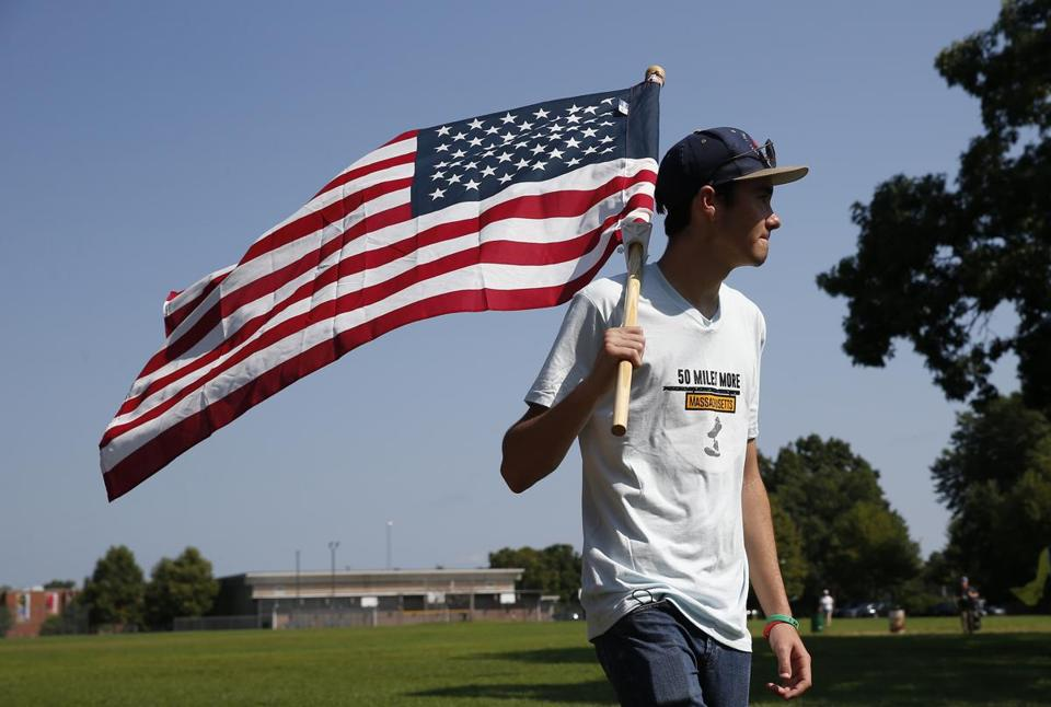 Springfield, MA--8/26/2018-- David Hogg picks up an American flag as a group of counter protesters arrive to the park where a group of teens marching to end gun violence had gathered to finish their 50 mile walk to Smith & Wesson. (Jessica Rinaldi/Globe Staff) Topic: 27teensmarch Reporter:
