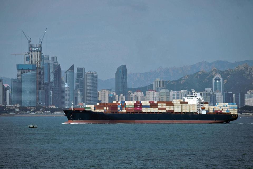 A container ship sailed by the business district in Qingdao in east China's Shandong province. Washington has invited Beijing to hold new talks on their escalating tariff dispute, the Chinese foreign ministry said Thursday, ahead of a decision by President Trump on whether to raise duties on $200 billion of Chinese imports.