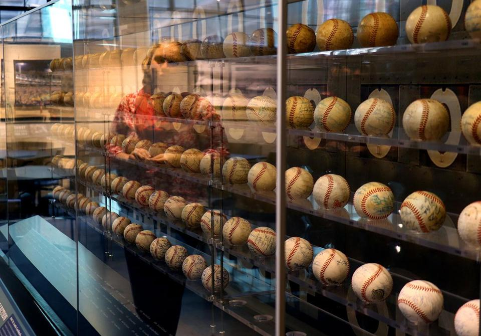 Red Sox curator is reflected in the display case of a collection of World Series baseballs at Fenway Park.