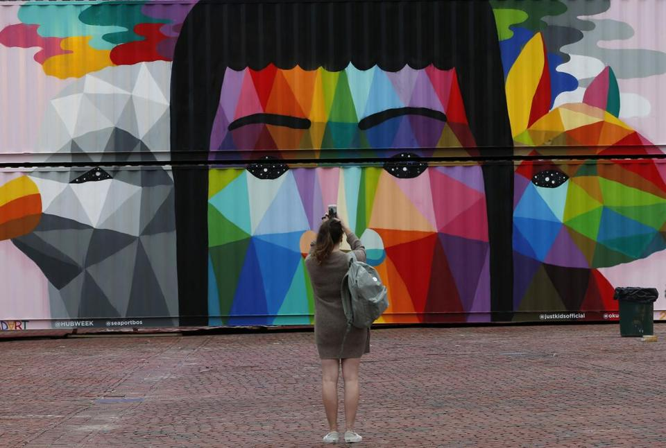 A woman stopped to take a photo of the feature wall painted by Okuda San Miguel.