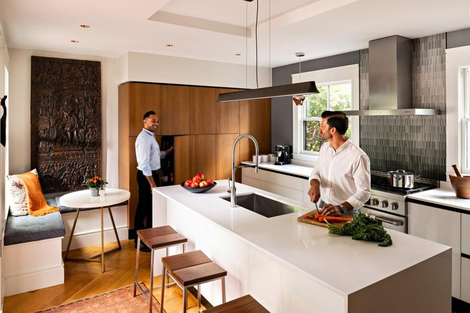 Anil Nair (left) and Philippe Saad in their kitchen, where Krishna watches over the breakfast nook. Walnut veneer on the tall wall cupboards balances the minimalist white back-painted glass lower cabinets. Above the Jenn-Air stove, the backsplash is a single sheet of thin porcelain that looks textured but is smooth to the touch.