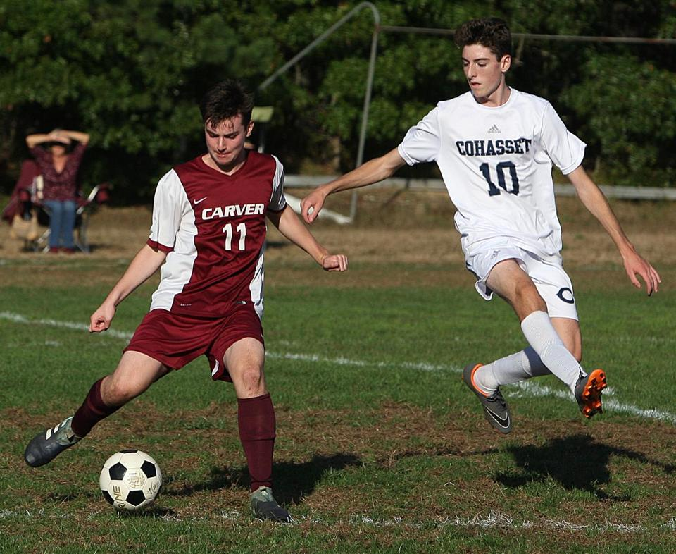 Above left, soccer player Dominic Craig, a sophomore at Carver High, goes up against Cohasset's Ben Smith. Above right, fellow Carver sophomore Mike Sawicki keeps the ball away from Cohasset's Jack Elliot.