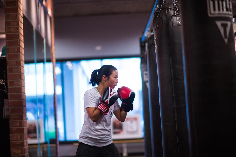 Jungeun Lee, a senior accountant at Corbus Pharmaceuticals practices her form during a boxing class at TITLE Boxing Club in Norwood., Tuesday, Oct. 9. 2018. Gretchen Ertl for The Boston Globe.