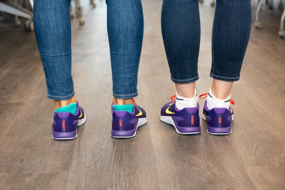 Two Tango employees wearing the shoes given this year to workers and based on the winning design of an employee. The shoes were given to associates to mark our move to our new space at 100 Binney Street. We held a contest for associates to design a pair of shoes and this was the winning design. When associates arrived at our new office location on June 4th, the shoes were set up at everyoneÕs desk. (Gigi de Manio/Tango)