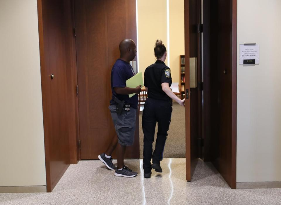 A police officer escorted people in and out of a courtroom at the Edward Brooke Courthouse in July.