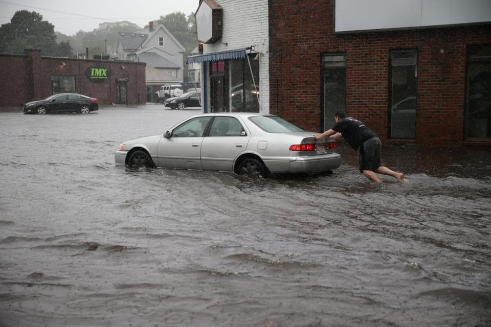A man pushed his car in Quincy during a September flash flood.