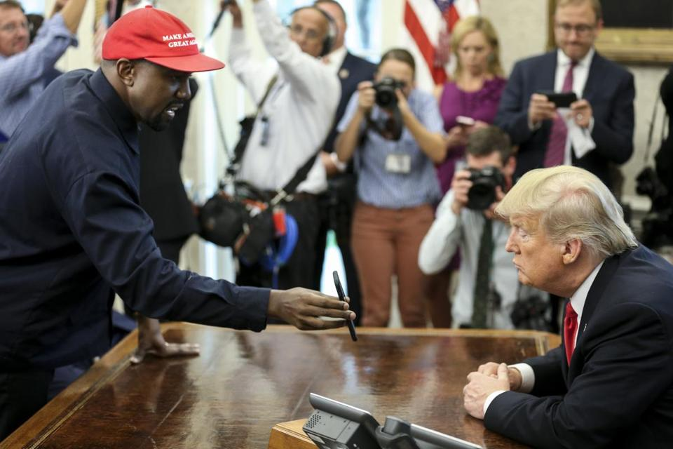 WASHINGTON, DC - OCTOBER 11: (AFP OUT) Rapper Kanye West , left, shows a picture of a plane on a phone to U.S. President Donald Trump during a meeting in the Oval office of the White House on October 11, 2018 in Washington, DC. (Photo by Oliver Contreras - Pool/Getty Images)