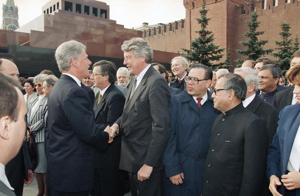 Then-Prime Minister Wim Kok of the Netherlands (center) shook hands with then-President Bill Clinton in Moscow's Red Square in 1995.