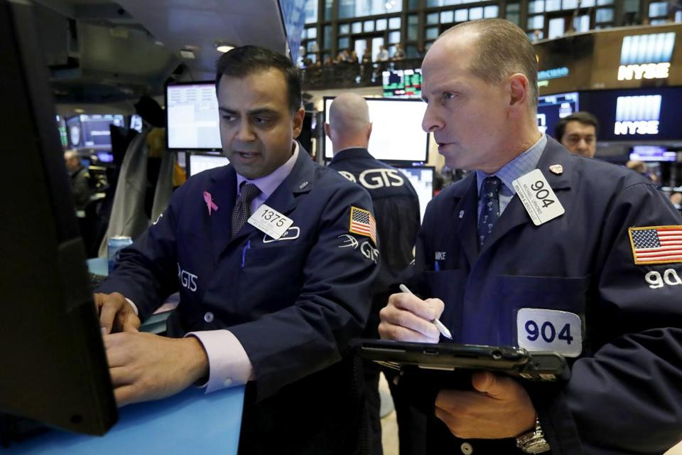 Specialist Dilip Patel, left, and trader Michael Urkonis work on the floor of the New York Stock Exchange, Friday, Oct. 26, 2018. Stocks are opening broadly lower on Wall Street, a day after a massive surge, as a number of big companies reported disappointing results. (AP Photo/Richard Drew)
