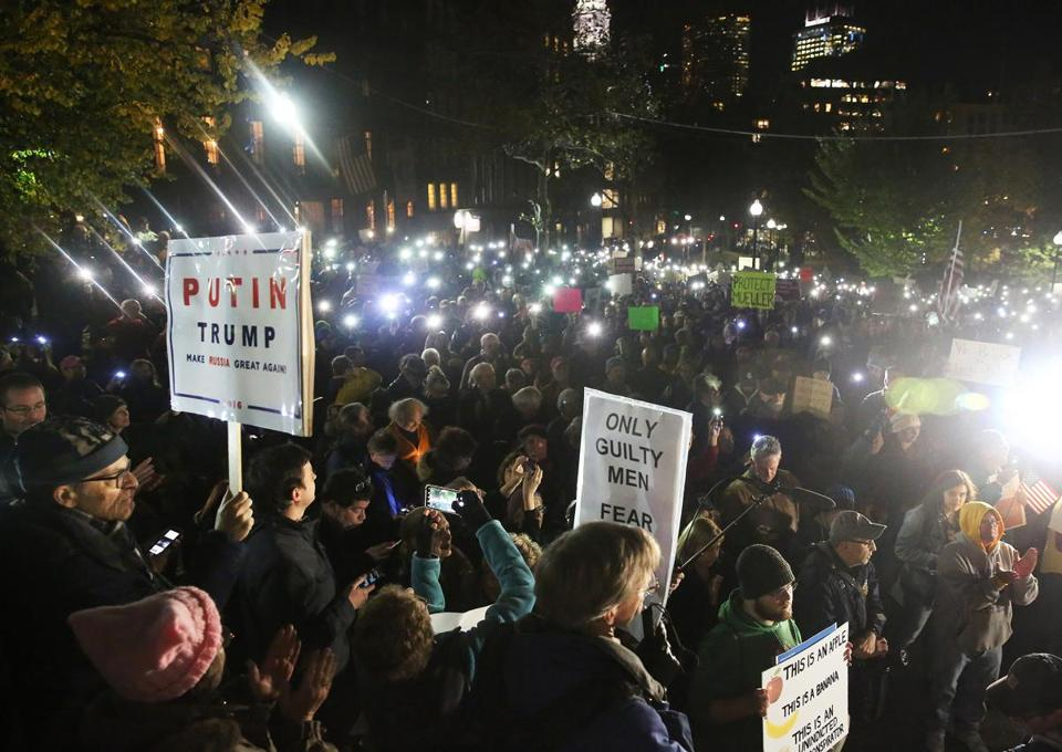 People are asked to hold up their lights. A protest to protect the Mueller investigation is held on Boston Common, across from the State House.