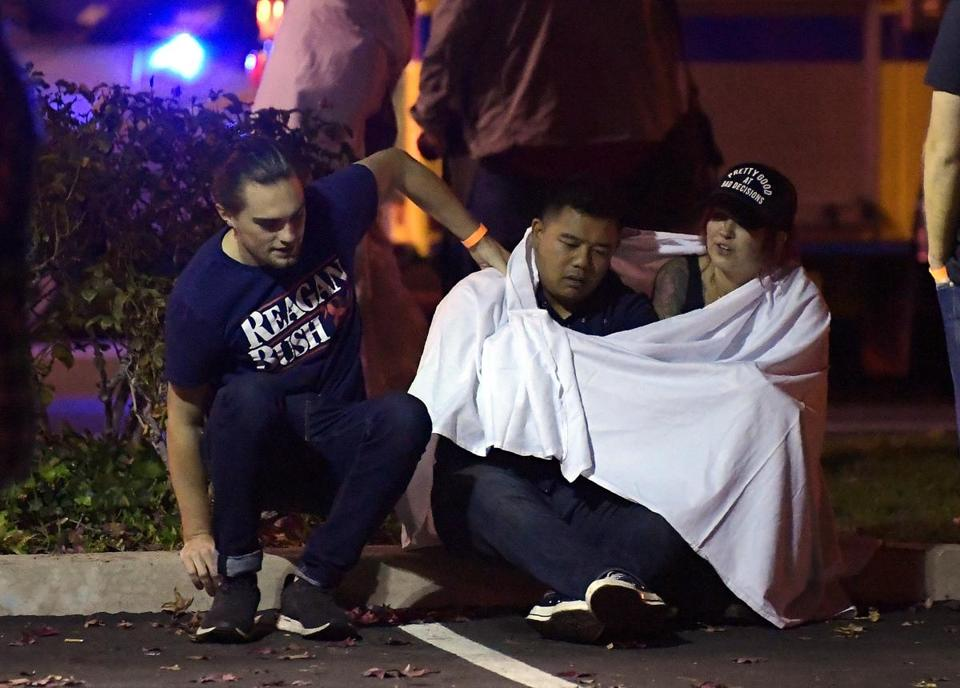 People comforted each other outside the scene of the mass shooting in Thousand Oaks, Calif., late Wednesday night.  where a gunman opened fire  inside a country dance bar crowded with hundreds of people.
