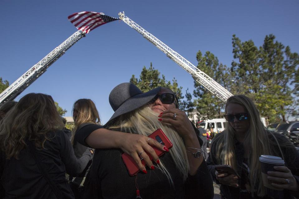 THOUSAND OAKS, CA - NOVEMBER 08: People hug after praying before the procession carrying the body of Ventura County Sheriffs Sgt. Ron Helus, who was killed in a mass shooting at the Borderline Bar and Grill, leaves Los Robles Hospital on November 8, 2018 in Thousand Oaks, California. Twelve people were killed, including the sergeant and the gunman, after a mass shooting at the Borderline Bar and Grill in Thousand Oaks late Wednesday night. (Photo by David McNew/Getty Images)