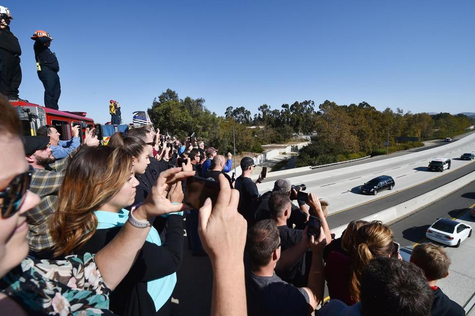 Firefighters, law enforcement and members of the public watch as the hearse carrying the body of Ventura County Sheriff's Sergeant Ron Helus, the first victim named in the mass shooting at a country bar in Thousand Oaks, California, in transported in a procession November 8, 2018. - The gunman who killed 12 people in a crowded California country music bar has been identified as 28-year-old Ian David Long, a former Marine, the local sheriff said Thursday. The suspect, who was armed with a .45-caliber handgun, was found deceased at the Borderline Bar and Grill, the scene of the shooting in the city of Thousand Oaks northwest of downtown Los Angeles. (Photo by Robyn Beck / AFP)ROBYN BECK/AFP/Getty Images
