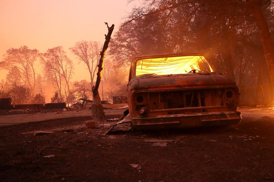 A burned-out van smoldered in Paradise, Calif., after a wildfire being called 'Camp Fire' moved through the area.