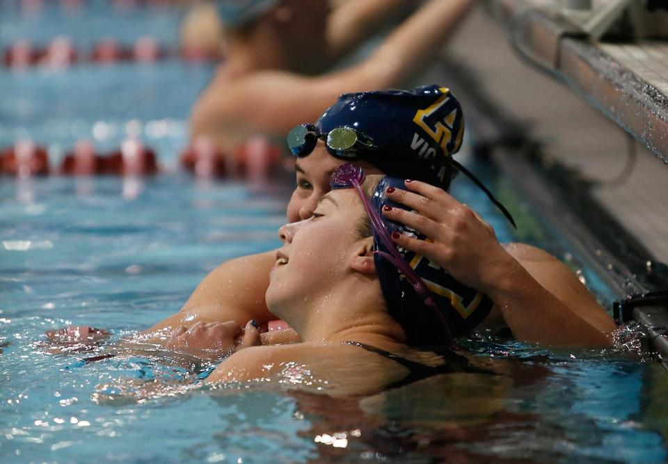 Boston, MA, 11/18/2018 -- Andover's Victoria Ambrose (L) hugs Andover teammate Charlotte Moulson reacts at the end of the Girls 500 Yard Freestyle at the MIAA All-State Division 1 Swimming and Diving Championships at Harvard's Blodgett Pool. (Jessica Rinaldi/Globe Staff) Topic: 19schswim Reporter: