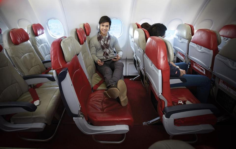 A man stretches out across empty airplane seats. As the number of passengers increases on flights, it's becoming rarer for passengers to wind up with an empty seat next to them, or better yet, their own row.