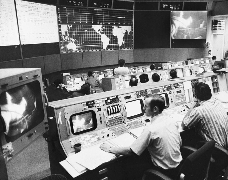 Ground controllers watch the space walk by Apollo 15 command module pilot Alfred M. Worden from Mission Control, Manned Spacecraft Center in Houston, Texas, Aug. 5, 1971. The spacewalk appears on the large televison screen in background and on smaller screens around the console. (AP Photo/NASA)