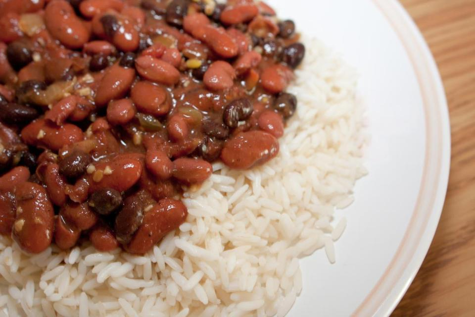 "Red beans and rice is strongly associated with both a city —New Orleans —and a day —Monday. Before washing machines were common, Monday was ""wash day."" Doing laundry by hand left little time to prepare food, so often cooks simmered a pot of red beans (frequently flavored with the bone from a Sunday ham dinner) unattended for much of the day. Even now some New Orleans restaurants still serve red beans and rice on Mondays."