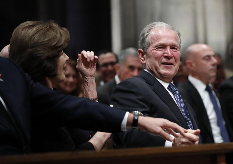 WASHINGTON, DC - DECEMBER 05: (AFP OUT) Former President George W. Bush smiles with former first lady Laura Bush during the state funeral for his father, former U.S. President George H. W. Bush, at the Washington National Cathedral on December 5, 2018 in Washington, DC. President Bush will be buried at his final resting place at the George H.W. Bush Presidential Library at Texas A&M University in College Station, Texas. A WWII combat veteran, Bush served as a member of Congress from Texas, ambassador to the United Nations, director of the CIA, vice president and 41st president of the United States. (Photo by Alex Brandon - Pool/Getty Images)