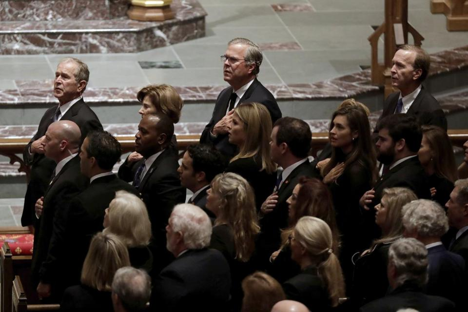 Former President George W. Bush, left, and his brothers former Florida Gov. Jeb Bush and Neil Bush, sing during a funeral for former President George H.W. Bush at St. Martin's Episcopal Church Thursday, Dec. 6, 2018, in Houston. (AP Photo/Mark Humphrey)