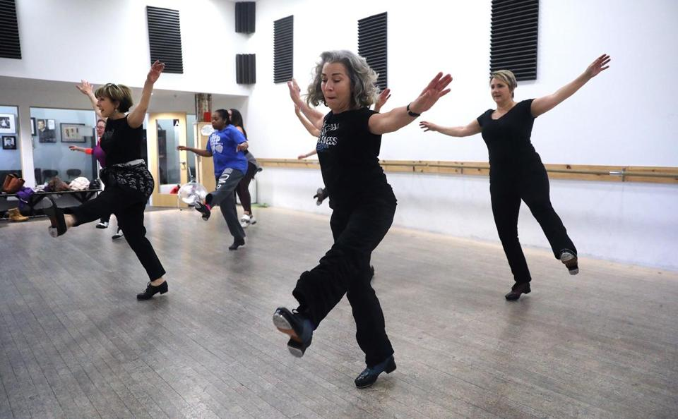 Somerville, MA - 12/6/18 Elaine Shannon (cq), center, kicks up her heels with the rest of the class. Intermediate and advanced tap students take a 90-minute class, at the Deborah Mason Performing Arts Center (cq), with instructor Julia Boynton (cq), left. Photo by Pat Greenhouse/Globe Staff Topic: ZoExerciseRegional Reporter: Brion O'Connor
