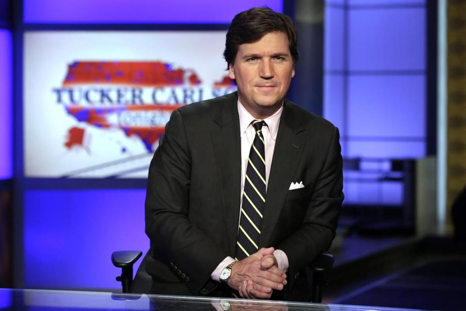 "FILE - In this March 2, 2017, file photo, Tucker Carlson, host of ""Tucker Carlson Tonight,"" poses for photos in a Fox News Channel studio in New York. Washington police are investigating a protest outside the home of Carlson as a possible hate crime. According to a police report, a group of demonstrators gathered outside Carlson's Northwest Washington home Wednesday night, Nov. 7, 2018. A video posted on social media but later removed shows people standing outside a darkened home chanting ""Tucker Carlson we will fight/We know where you sleep at night."" (AP Photo/Richard Drew, File)"
