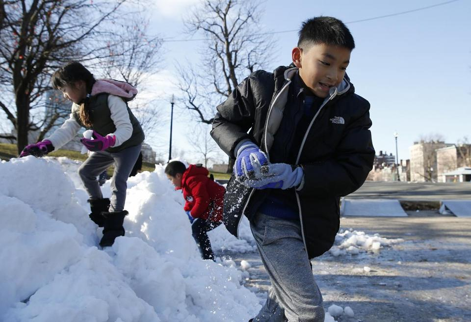 Boston, MA, 12/30/2018 -- Alfred, of Florida (R) formed a snowball in his hands as he played with other children on a pile of snow left by the zamboni near the Frog Pond. (Jessica Rinaldi/Globe Staff) Topic: 31firstnight Reporter: