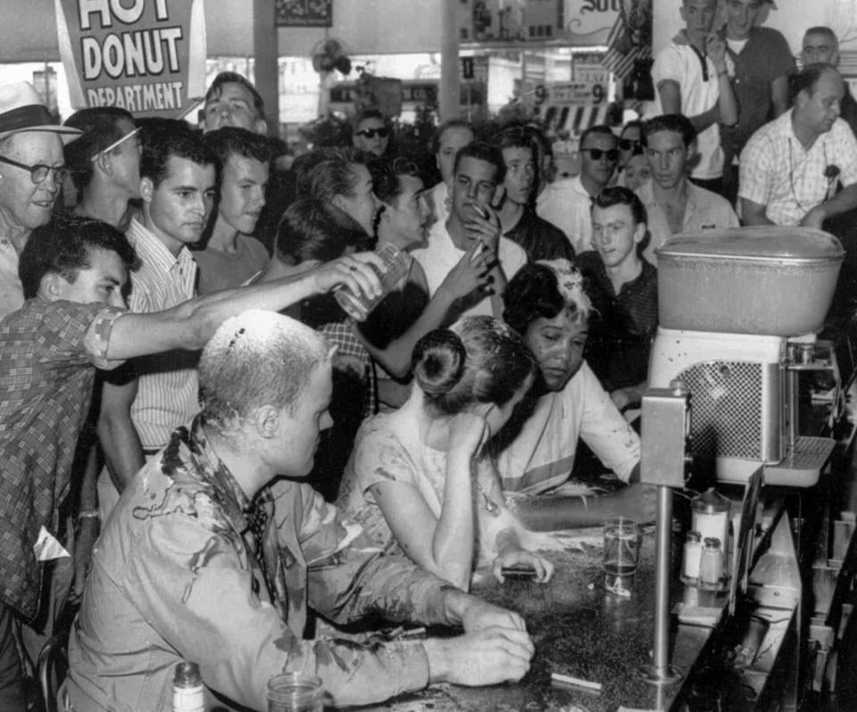 FILE - In this May 28, 1963 file photo, a group of whites pour sugar, ketchup and mustard over the heads of Tougaloo College student demonstrators at a sit-in demonstration at a Woolworth's lunch counter in Jackson, Miss. Seated at the counter, from left, are Tougaloo College professor John Salter,and students Joan Trumpauer and Anne Moody. John Salter, who also used the name John Hunter Gray, died Monday, Jan. 7, 2019 at his home in Pocatello, Idaho. Relatives say he was 84 when he died Monday after an illness. (Fred Blackwell/The Clarion-Ledger via AP, File)