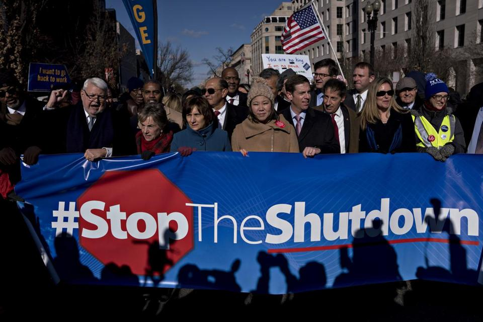 "Demonstrators hold a ""#Stoptheshutdown"" sign during a rally with union members and federal employees."