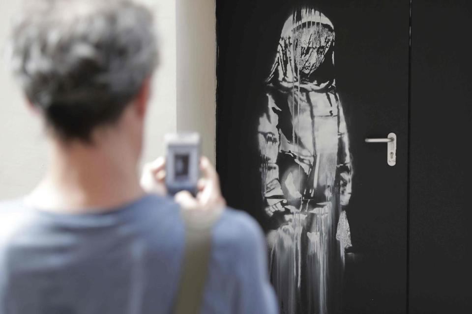 A man took a photograph of the artwork in Paris in June, 2018.