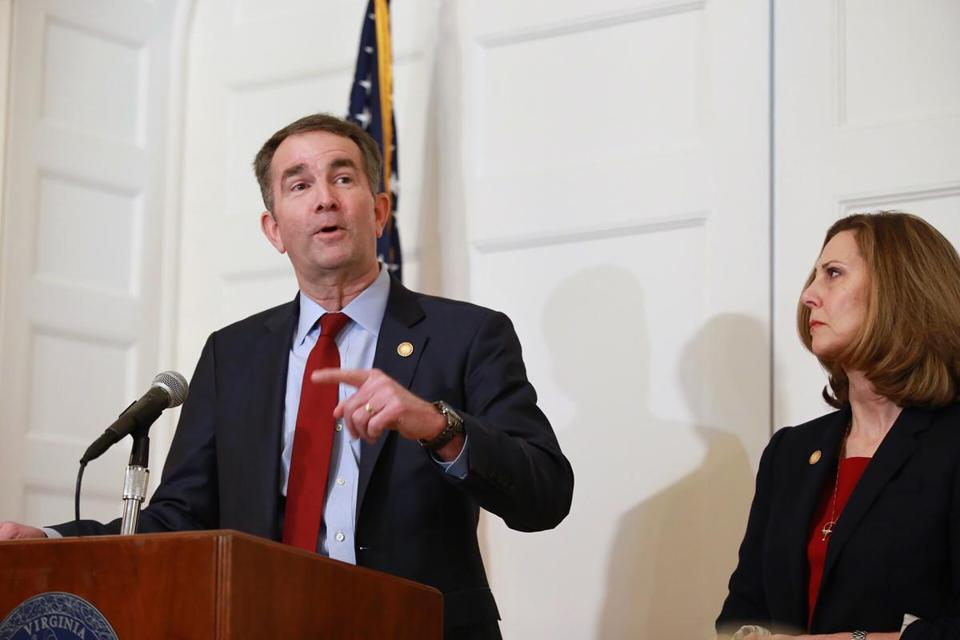Gov. Ralph Northam of Virginia speaks during a press conference next to his wife Pam in Richmond Va. Feb. 2 2019. Northam facing pressure from his own party to resign said Saturday Feb. 2 2019 he would not quit and denied that he appeared in Ku