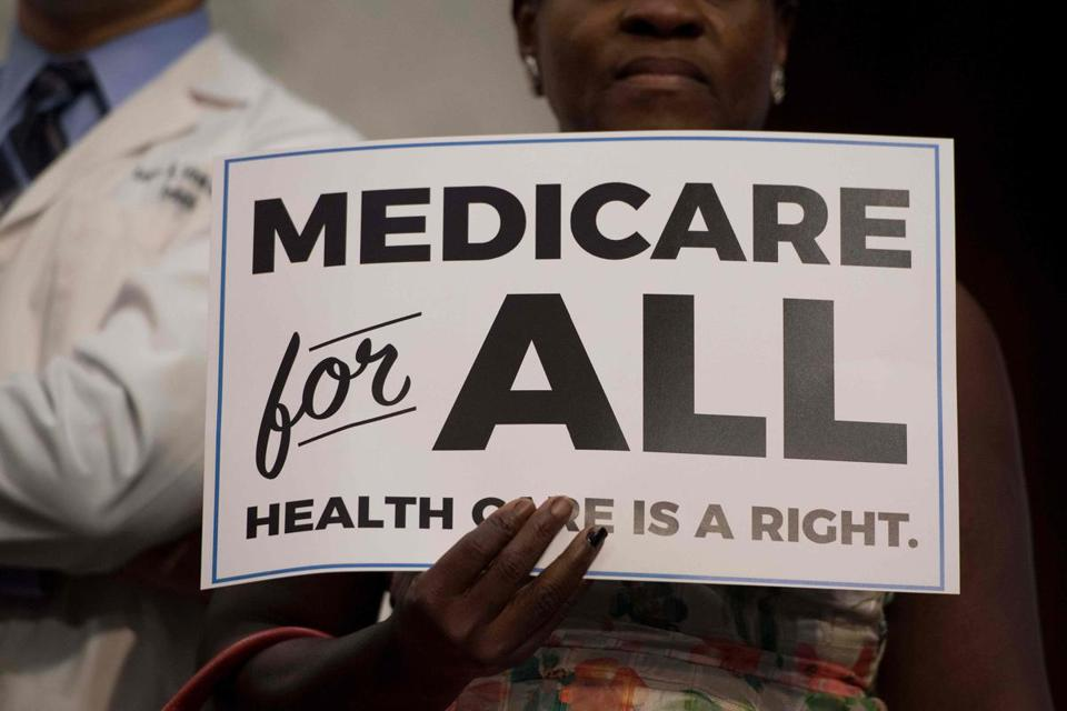 "(FILES) In this file photo taken on September 13, 2017 a member of the audience holds up a placard as US Senator Bernie Sanders, Independent from Vermont, discusses Medicare for All legislation on Capitol Hill in Washington, DC. - Having a health insurance card in America is no guarantee of medical care without the risk of financial ruin. One must take care to choose a doctor or hospital that is part of a pre-approved network. Estimate how much would be paid out of pocket after hospital bills that can reach tens of thousands of dollars. And, for Americans covered by their employers, be careful about any change in jobs and try to avoid risky gaps in health insurance coverage.Vermont Senator Bernie Sanders, who came up with the idea, California Senator Kamala Harris and New York Senator Kirsten Gillibrand are among those calling for ""Medicare for all,"" or offering everyone in the nation the type of public insurance offered to those over 65, a program in existence since the 1960s. (Photo by JIM WATSON / AFP)JIM WATSON/AFP/Getty Images"