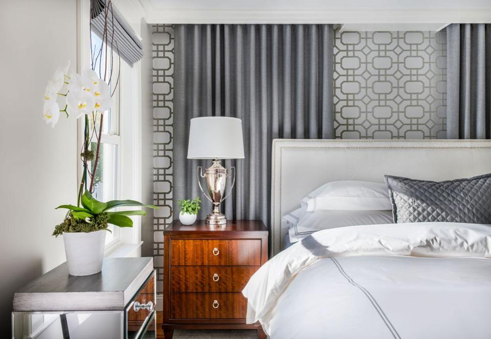 AFTER: Fulmer hung drapery panels behind the bed on two sides, even though only one covers a window. The geometric wallpaper is Portier Flock by Thibaut.