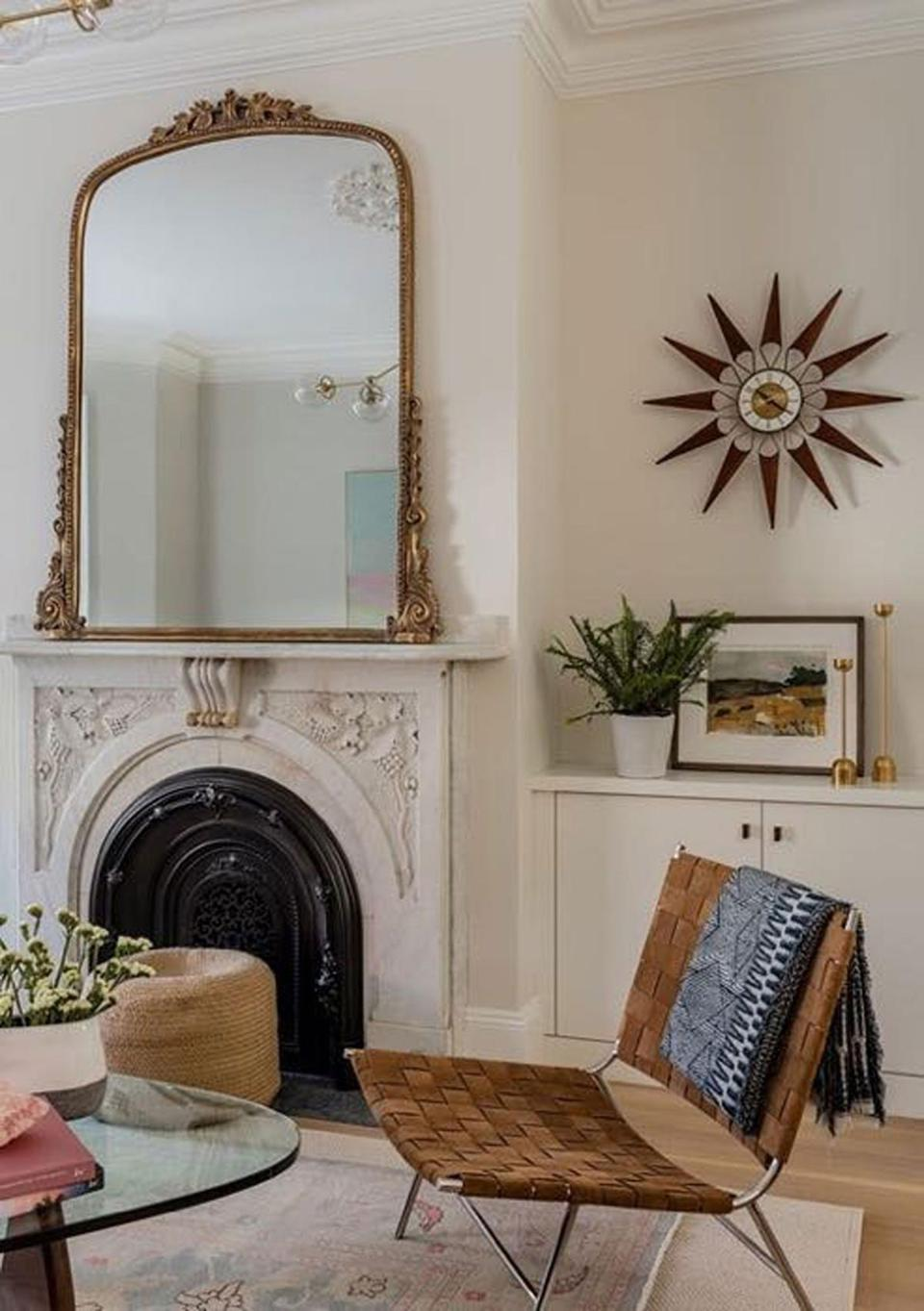 AFTER: In the living room, an ornate gold-framed mirror from Anthropologie now adorns the original stone mantel, and a vintage 1950s brass-and-teak starburst wall clock by Elgin hangs over a new built-in cabinet.