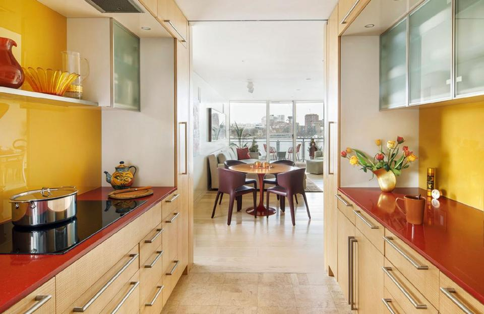 AFTER: Annette displays pieces from her glass collection on the shelf above the cooktop in the sleek new galley kitchen. The eggplant-colored leather chairs at the breakfast table are by Cassina, from Casa Design in SoWa.