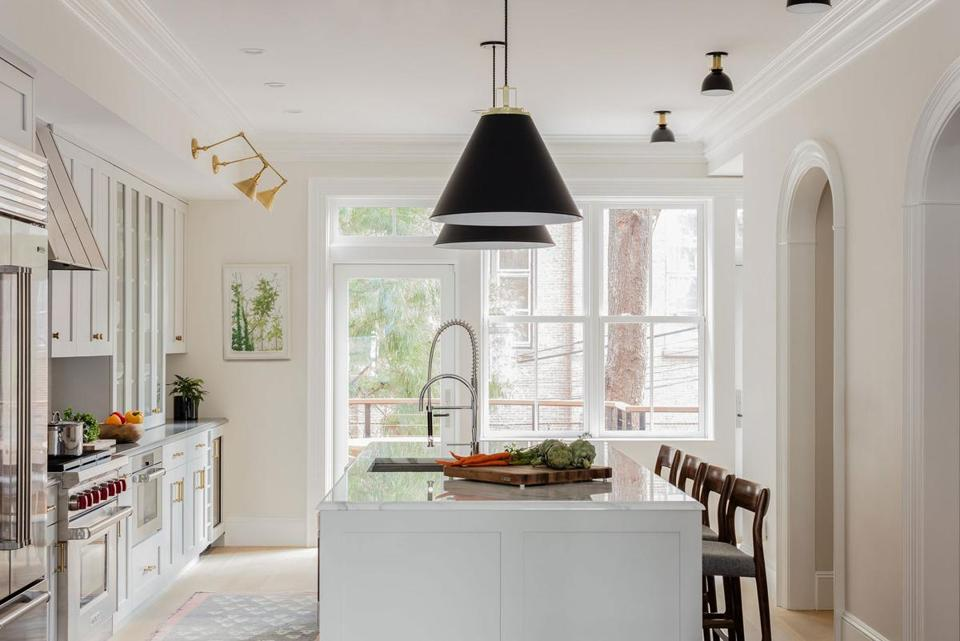 Ralph Lauren swing-arm sconces highlight the china cabinet, and oversize aluminum pendant lights from Rejuvenation hang over the island. Simple flush-mount fixtures from Schoolhouse illuminate the counter seating.