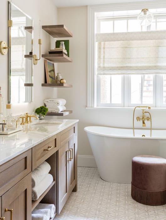 "Brass fixtures, including sconces from Cedar & Moss, adorn the master bath. It has a cerused oak vanity, a marble mosaic tile floor, and oversize windows behind a sculptural soaking tub. ""It's all about warm tones,"" says Vieira."