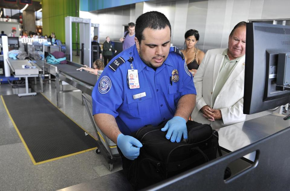 A TSA Agent checked the carry-on bag of a passenger at Logan Airport in Boston