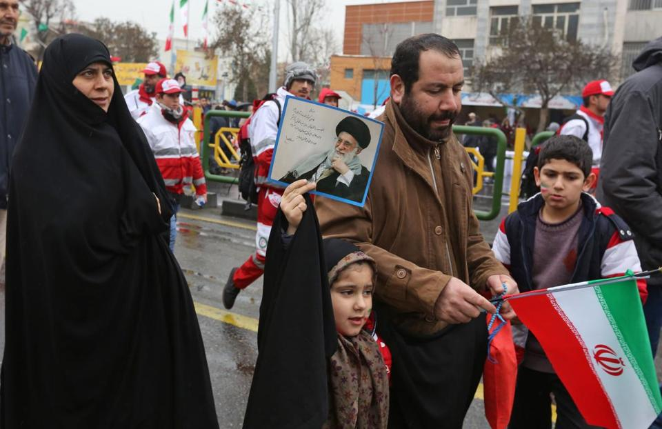 An Iranian girl held up a portrait of the country's Supreme Leader Ali Khamenei as she marched in Tehran on Monday.