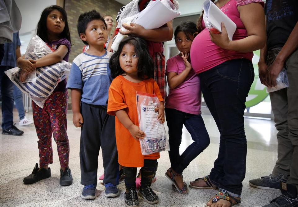 A family, processed by US Border Patrol in McAllen, Texas, waits for their next journey.