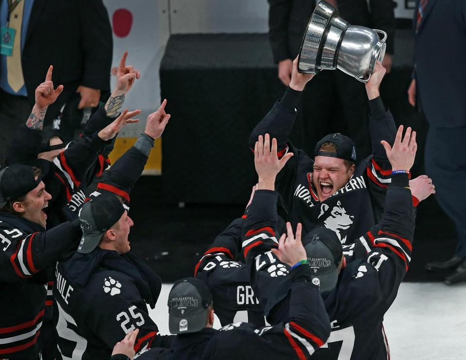 Northeastern captain Eric Williams hoists the Beanpot trophy as the Huskies celebrate their sixth title.