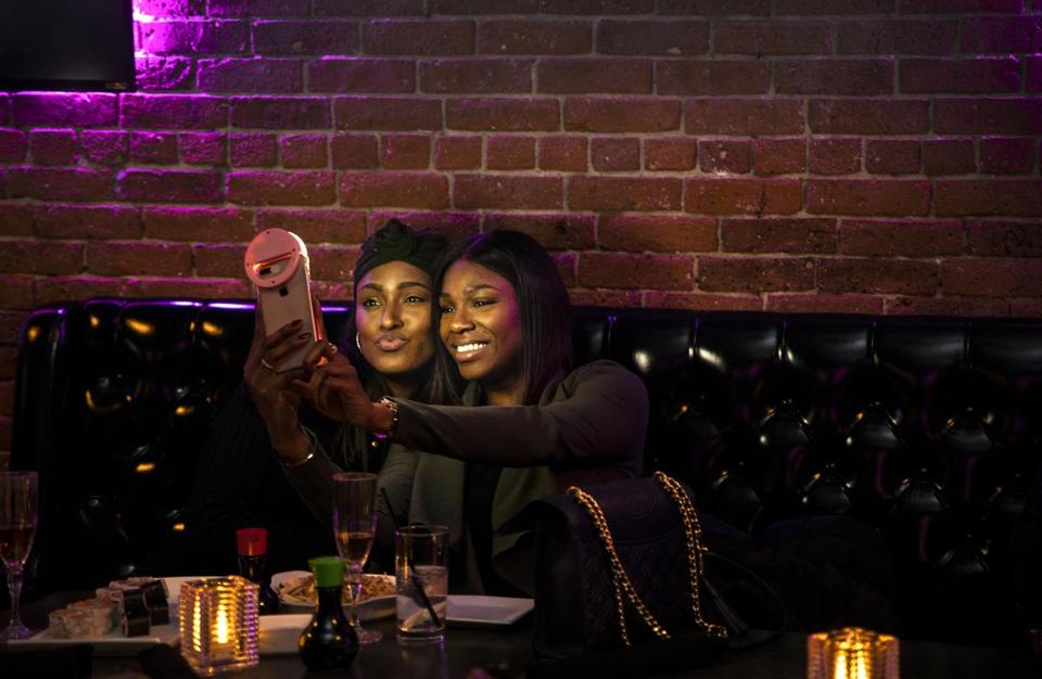 BOSTON, MA - 02/20/2019 Natalee Pennicooke, left, and Melanie Amarante snap a selfie at the Toast to Black Excellence event at 2Twenty2 Lounge held by Farrah Belizaire and her company LiteWork. The event was created with the mission to diffuse the narrative that says Boston is a white and racist city and create visibility for diversity and black millennials. (Erin Clark for The Boston Globe)