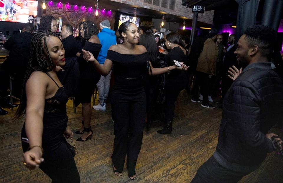 BOSTON, MA - 02/20/2019 Philomena Nwanze, left, Jamon Patterson, center, and Philip Washington dance at the Toast to Black Excellence at 2Twenty2 Lounge held by Farrah Belizaire and her company LiteWork. The event was created with the mission to diffuse the narrative that says Boston is a white and racist city and create visibility for diversity and black millennials. (Erin Clark for The Boston Globe)