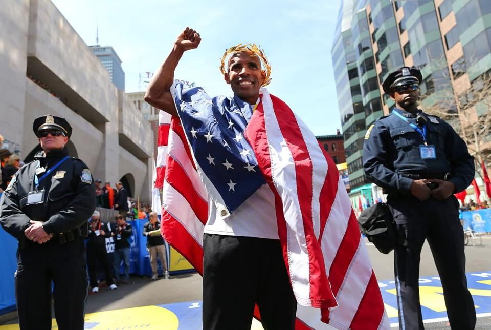 Boston04/21/14- At the Boston Marathon at the finish line ground level on Boylston Street mens winner Meb Keflezighi hold the flag up at the victory ceremony. Boston Globe staff photo by John Tlumacki(metro)