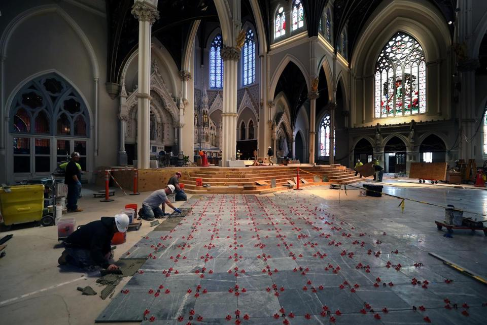 As part of the renovation of the Cathedral of the Holy Cross in Boston, workmen are installing the new marble floors, original pews, exterior lighting, and video and audio technologies.